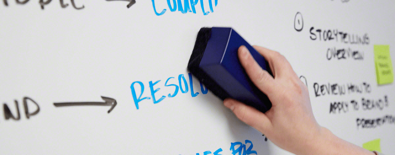 Blue and black marker writing on a whiteboard being erased with a dry erase marker