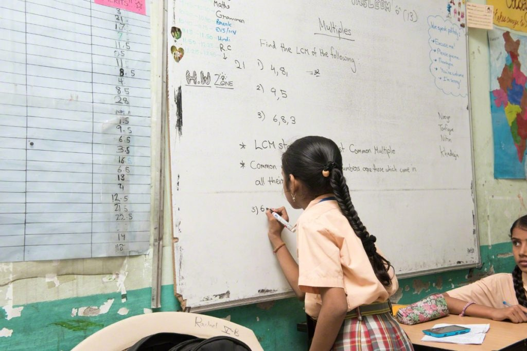 Young girl writing on whiteboard in Indian classroom with black marker