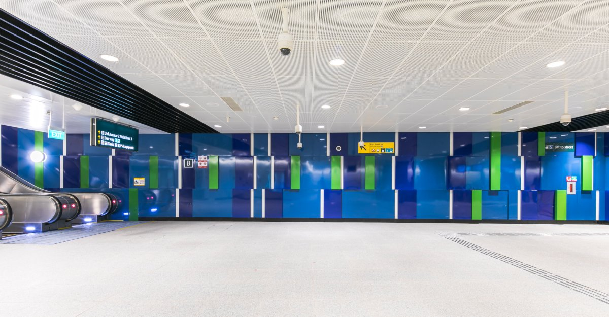 Combinations of blue and green panels on a wall in a train station with directional signs