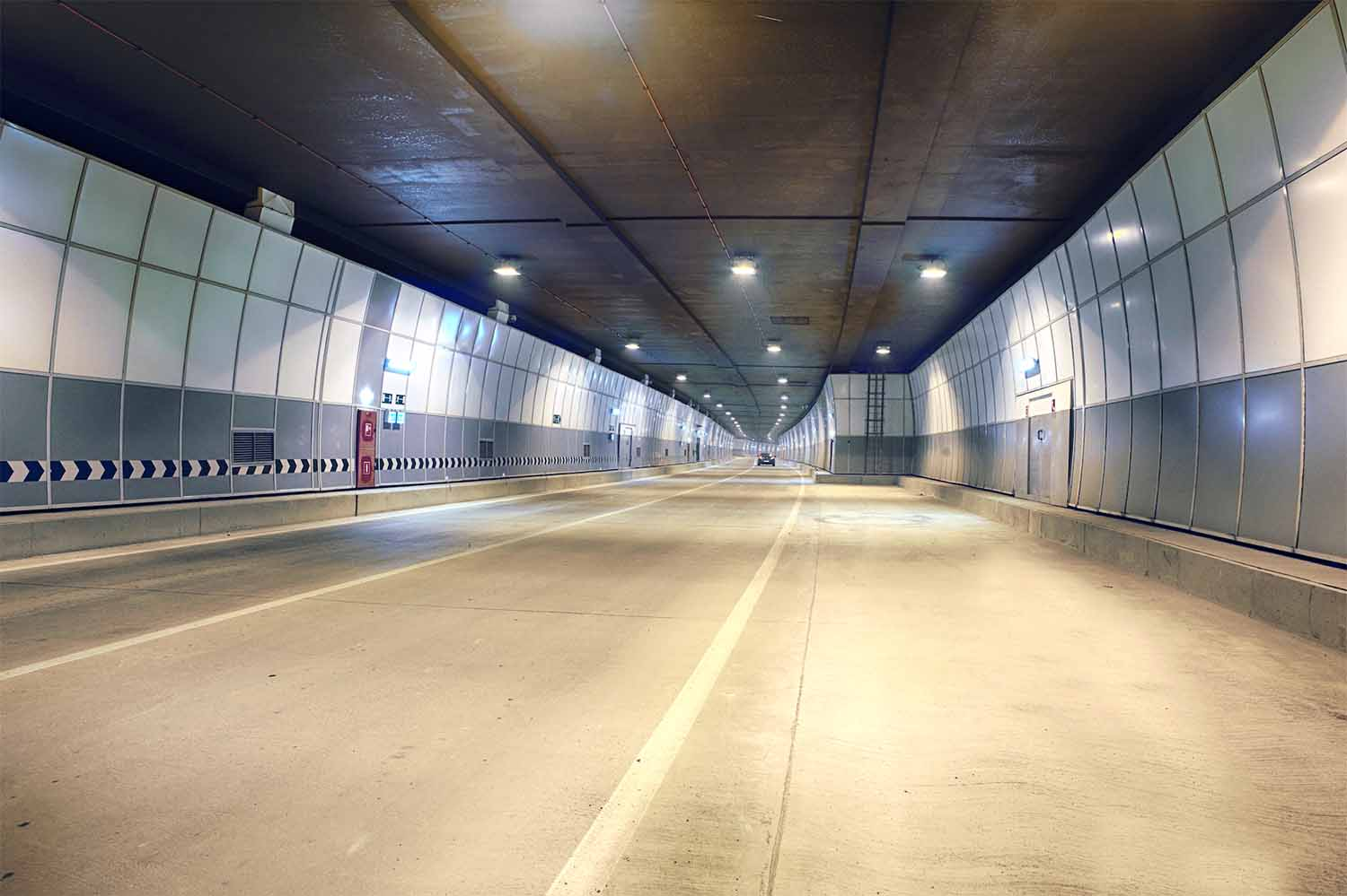 Car driving through two lane tunnel with durable wall panels on the sides