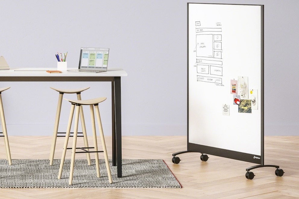 Mobile whiteboard on wheels next to tall table with wooden stools