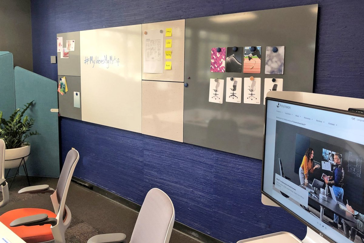 Magnetic whiteboard panels mounted to larger board on blue wall in meeting room, with nearby monitor and meeting room chairs