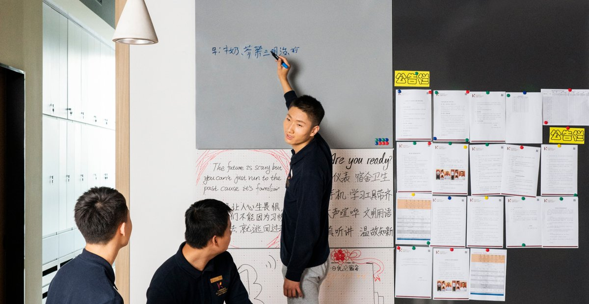 Young man writing on whiteboard at Kadoorie Youth Development Center