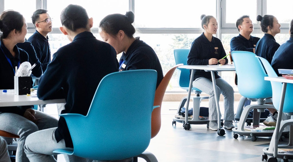 Students sitting in mobile chairs at desks in small groups